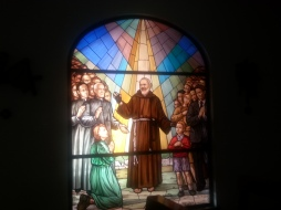 Stained glass Padre blessing girl